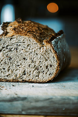 Close up of moody rustic sourdough bread cut open with seeds in crumb - p1166m2236607 by Cavan Images