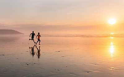 Athletes couple running on the beach at sunset - p300m1166558 by Marco Govel