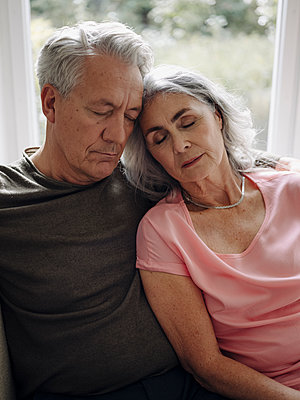 Senior couple napping on couch at home - p300m2154988 by Gustafsson