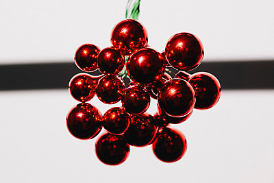 Close-up of red shiny Christmas ornament against white background - p301m1130923f by Halfdark