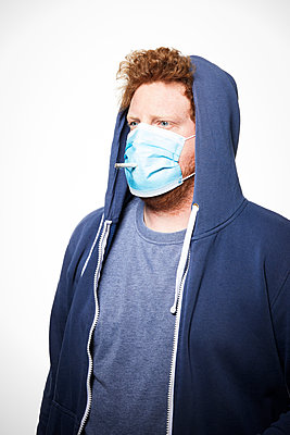 Man with surgical mask and cigarette, portrait - p930m2253769 by Ignatio Bravo