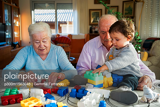 Great-grandparents and baby girl playing together with plastic building bricks at home - p300m1563048 by Gemma Ferrando