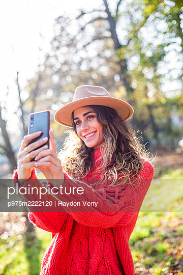 Young woman in red jumper takes a selfie - p975m2222120 by Hayden Verry