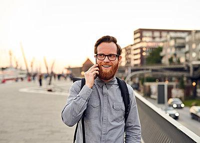 Mann telefoniert auf dem Arbeitsweg - p1124m1169981 von Willing-Holtz