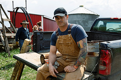 Portrait confident male farmer with tattoos sitting at truck bed on sunny farm - p1192m2109722 by Hero Images
