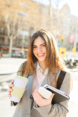 Spain, Barcelona, portrait of laughing young businesswoman with coffee to go - p300m1587132 by Valentina Barreto