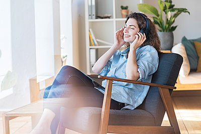 Smiling beautiful woman listening music through headphones while sitting on chair at home - p300m2276474 by Steve Brookland