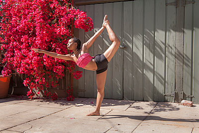 Woman practicing yoga near flowers and fence - p555m1409582 by Shestock