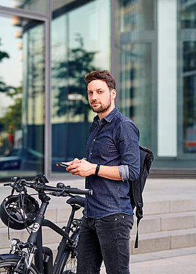 Bicycle courier using smartphone - p1124m2052999 by Willing-Holtz