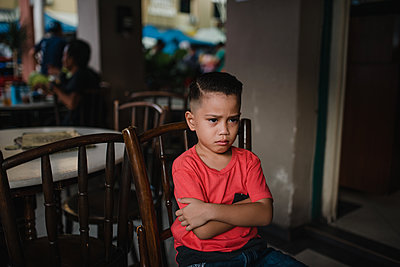 Asian boy sitting on a chair - p1166m2131306 by Cavan Images