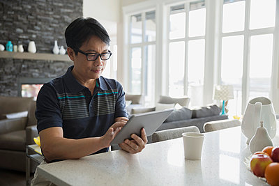 Man with eyeglasses using digital tablet kitchen island - p1192m1006047f by Hero Images