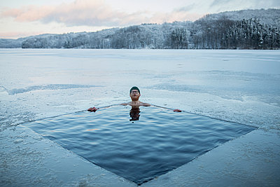 Man swimming in frozen lake - p312m2262885 by Anders Andersson