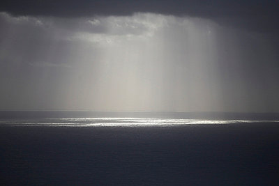 Sun Rays Reflected on Ocean Through Gray Clouds - p694m663680 by Maria K