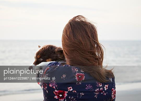 Frau hält Hundewelpen auf dem Arm - p1124m1223987 von Willing-Holtz