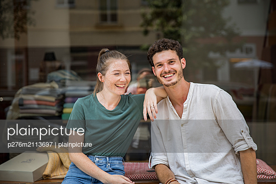 Young couple laughing together - p276m2113697 by plainpicture