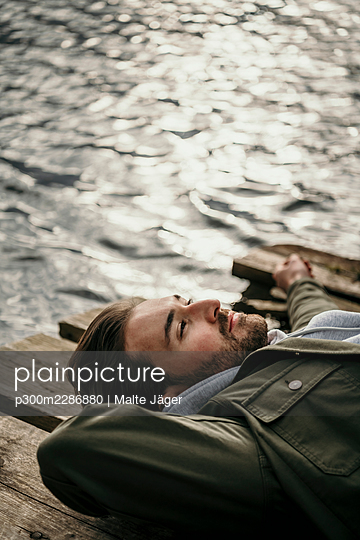 Smiling man day dreaming while lying on jetty over Seddinsee - p300m2286880 by Malte Jäger