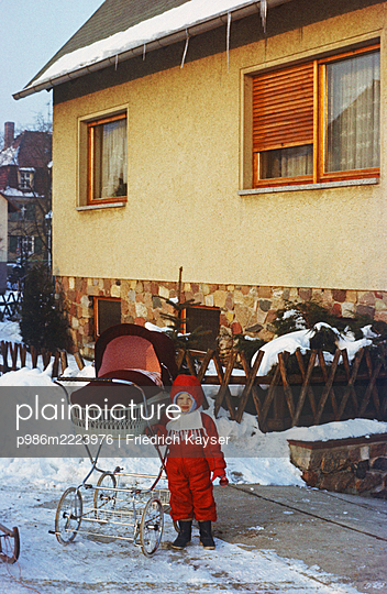 Germany, Boy in snow suit with pram in the GDR - p986m2223976 by Friedrich Kayser