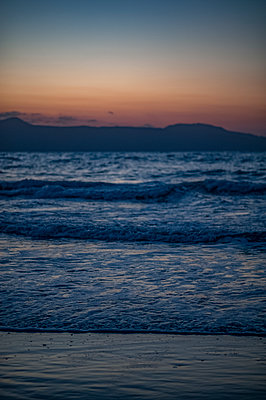 Shoreline and sea at dusk with hills in the background - p1047m1452295 by Sally Mundy