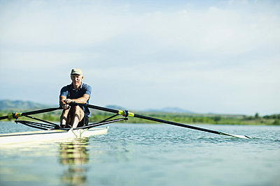 A middle-aged man rowing a single scull rowing boat on the water.  - p1100m876299f by Jamie Kripke