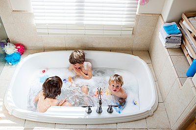 Overhead view of brothers playing in bathtub while bathing at home - p1166m1186803 by Cavan Images