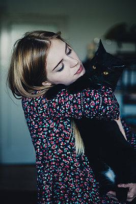 Junge Frau mit einem schwarzen Kater im Arm - p1184m1424463 von brabanski