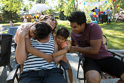 Happy, playful family at summer neighborhood block party in park - p1192m2017008 by Hero Images