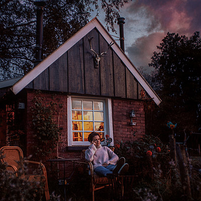 Woman sits in front of her hut in a market garden - p1551m2199963 by André Eikmeyer