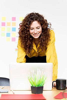Smiling woman working on laptop at desk in office - p300m2155042 by Francesco Morandini