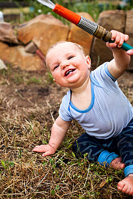 A laughing baby boy holding a garden hose - p301m799530f by Tobias Titz