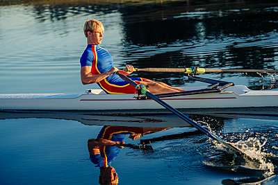 Caucasian man rowing on river - p555m1303398 by Pete Saloutos