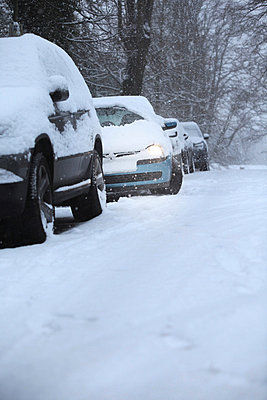 Car stuck in snow covered street - p924m806966f by Simon Battensby