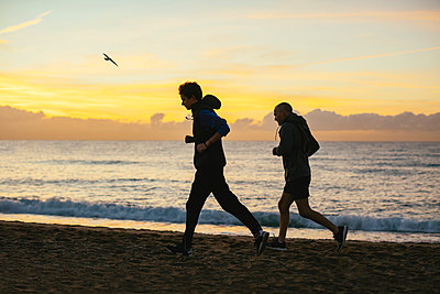 Side view of father and son jogging at beach against cloudy sky during sunset - p1166m1508168 by Cavan Images