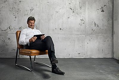 Mature man using digital tablet in front of concrete wall - p300m1580912 von Philipp Dimitri
