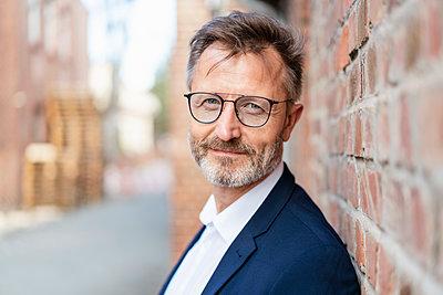 Portrait of confident businessman at brick wall - p300m2102998 by Daniel Ingold