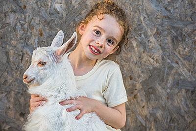 Portrait of cute girl holding baby goat outdoors - p301m961123f by Vladimir Godnik