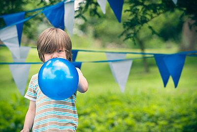 Boy blowing up balloon outdoors - p429m746868f by Colin Hawkins