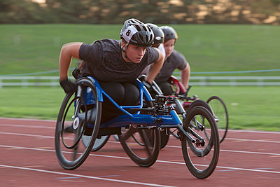 Determined young female paraplegic athlete speeding along sports track in wheelchair race - p1023m2067560 by Martin Barraud