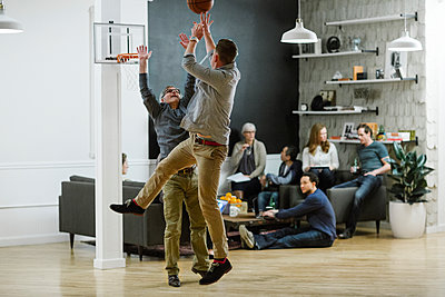 Businessmen playing basketball while colleagues sitting in background at office - p1166m1423455 by Cavan Images