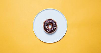 Overhead view of chocolate donut with sprinkles in plate on yellow background - p1166m2025505 by Cavan Images