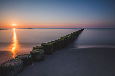 Germany, Mecklenburg-Western Pomerania, Wustrow, Baltic Sea, breakwater at sunset in winter - p300m2079160 by Anke Scheibe