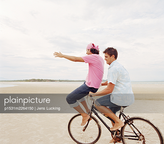 Young Man Cycling With Young Man Balancing On Handlebars On Beach - p1531m2264150 by Jens Lucking