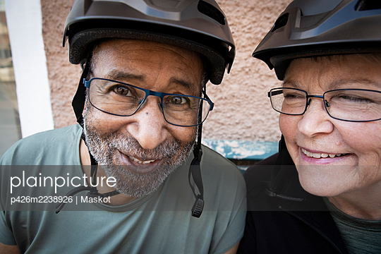 Smiling couple with cycling helmet outside house - p426m2238926 by Maskot
