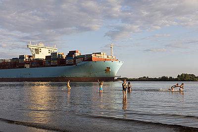 Kinder am Elbstrand mit Containerschiff - p076m2014662 von Tim Hoppe