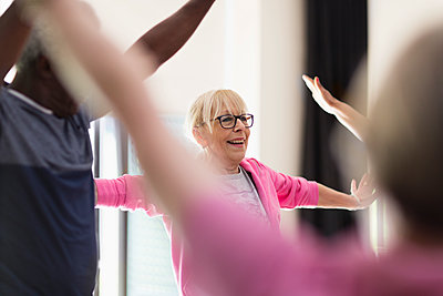 Smiling active senior woman stretching arms in exercise class - p1023m2017282 by Martin Barraud