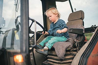 Kleiner Junge spielt auf einem Traktor - p1046m1220958 von Moritz Küstner