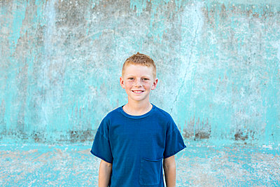 Portrait of a boy with red hair with a blue shirt and blue background - p1166m2078289 by Cavan Images