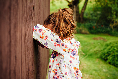 Girl leaning against wooden wall hiding her face - p300m1587279 von Annie Hall