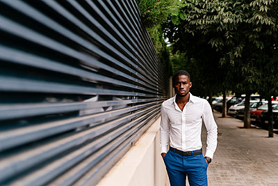 Confident African professional standing with hands in pockets by surrounding wall in city - p300m2220701 by Ezequiel Giménez