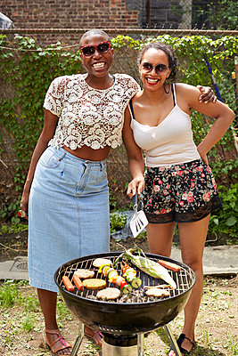 Women grilling vegetables at backyard barbecue - p555m1409860 by Granger Wootz