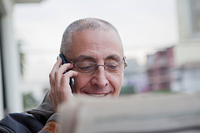 Hispanic senior man talking on cell phone and reading newspaper - p555m1421298 by REB Images